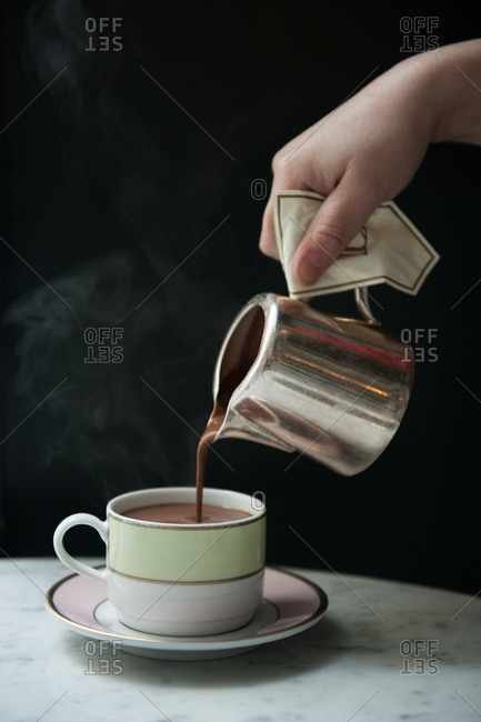 A hand pouring steaming hot chocolate into a mug