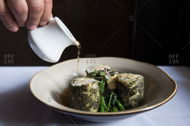 A chef pouring broth over pork dish
