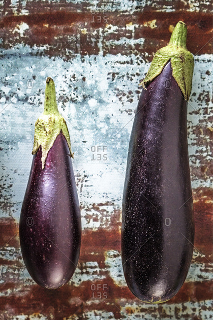 Two eggplants on a rusty surface