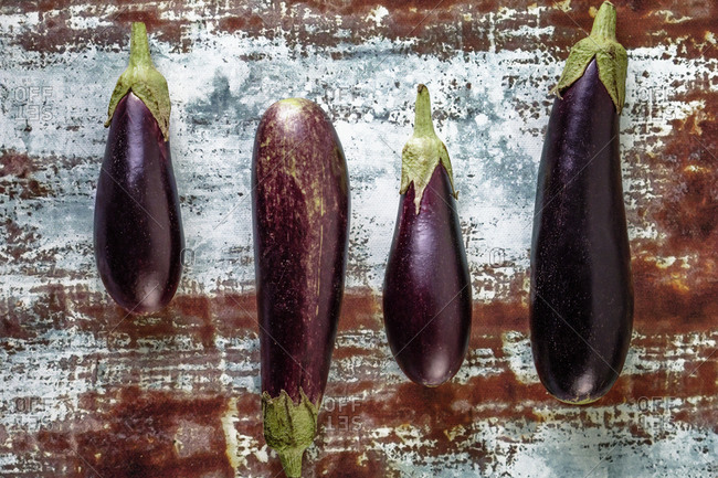 Four aubergines on a rusty surface