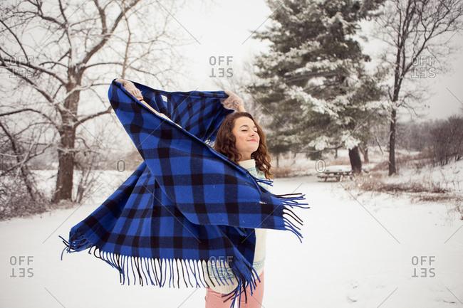 Girl twirling shawl in winter field