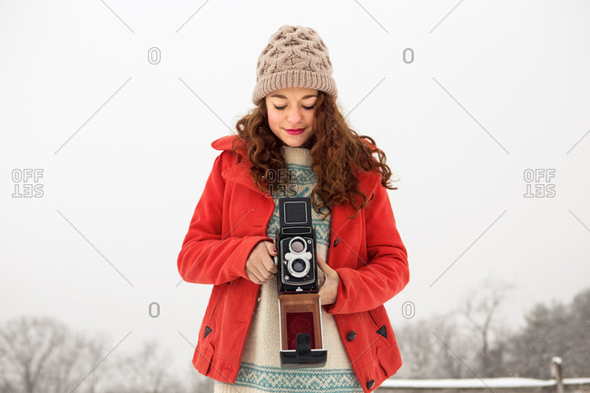 Girl in winter field with old camera