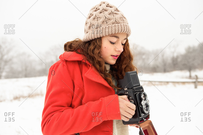 Girl in snowy field with old camera
