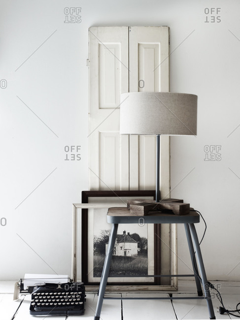 Arrangement of vintage typewriter, table, lamp and framed photo against a panel door