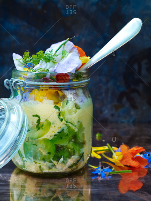 Salad in a jar topped with herbs and edible flowers