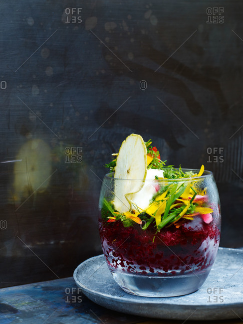Beet salad topped with flowers and pear slice served in a glass dish