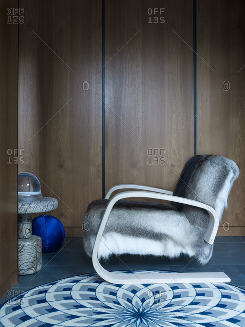 Paneled room with geometric rug and fur upholstered chair