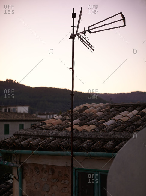 Windmill outside a rustic stone cottage with tile roof