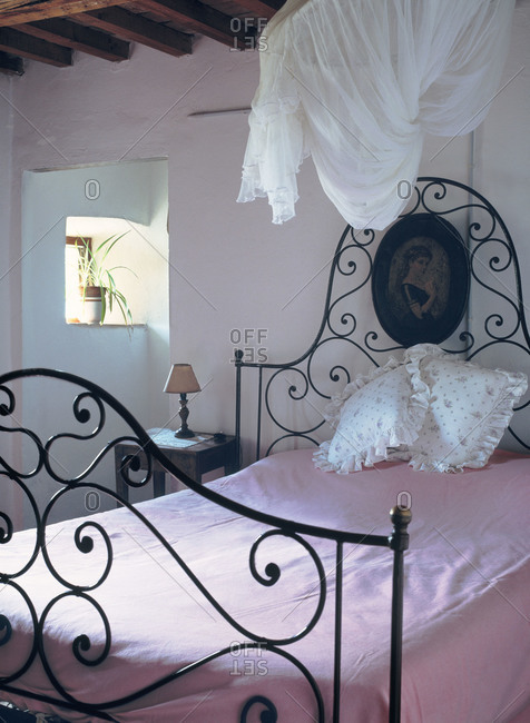 Room with an iron bed and pink blanket