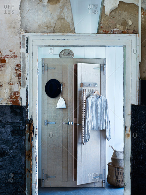 Doorway in a rustic stucco wall into a room with wardrobe