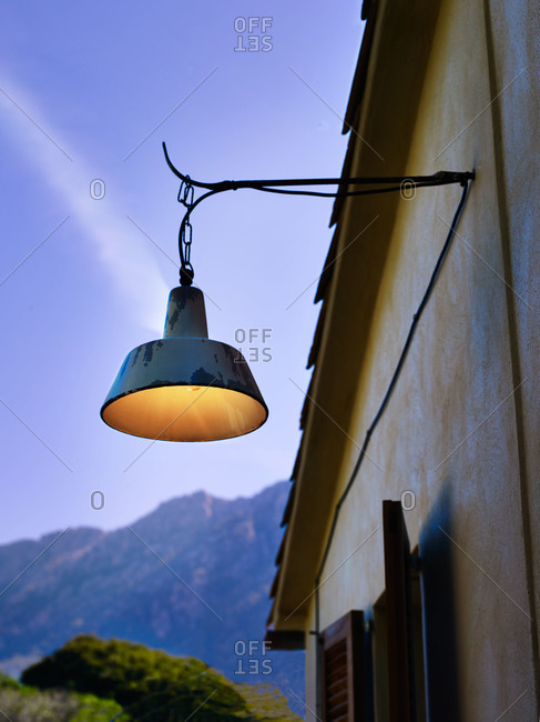 Old weathered lamp hanging off a stucco cottage
