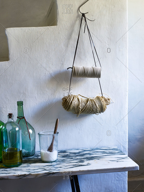 Twine hanging above marble table with bottles of olive oil and salt