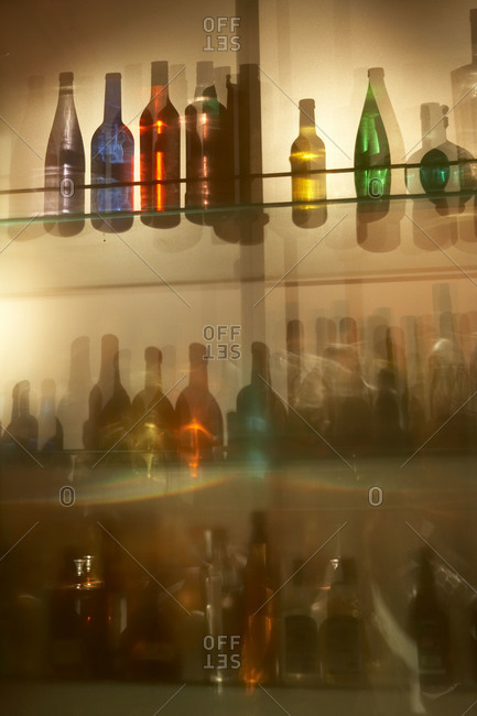 Different colored glass bottles seen through a translucent bar window