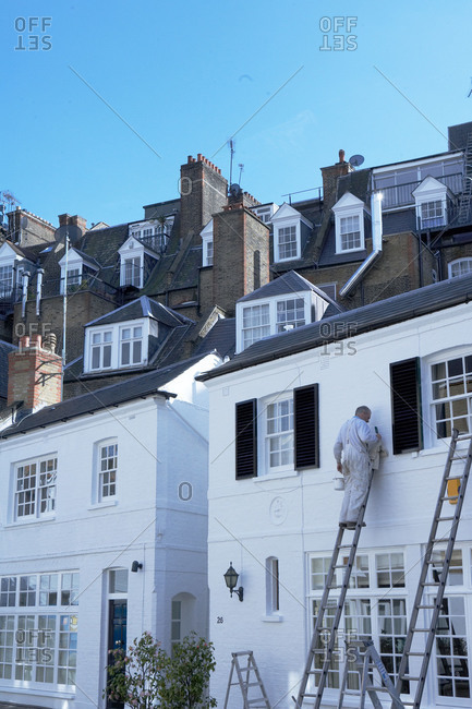 London, United Kingdom - March 16, 2007: Painter on a ladder in front of rows of old buildings