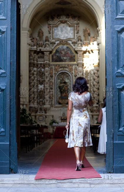 Back view of a woman walking into a church doorway