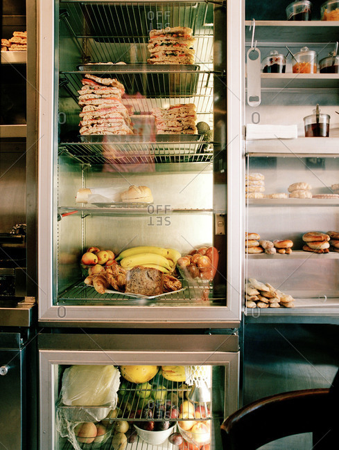 Commercial refrigerators filled with stacks of sandwiches