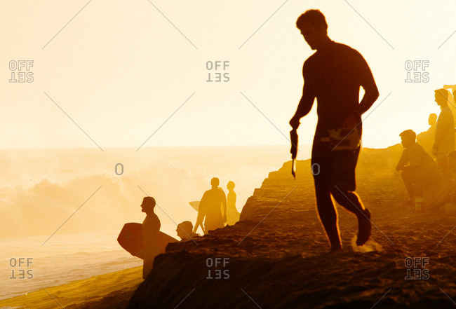 Backlit view of men on beach watching the surf