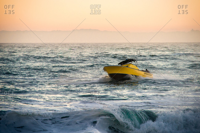 Yellow lifeguard boat patrols the water at sunset
