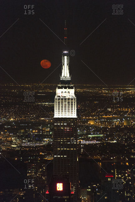 New York City, NY, USA - April 27, 2013: A view of the Empire State Building with a full moon