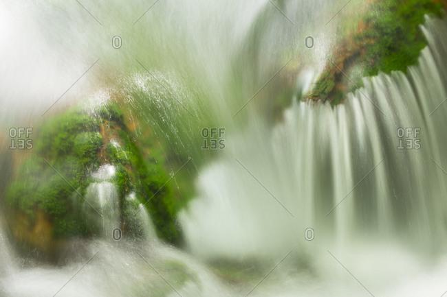 Close up of water rushing over moss covered rocks in Urabandai, Fukushima, Japan