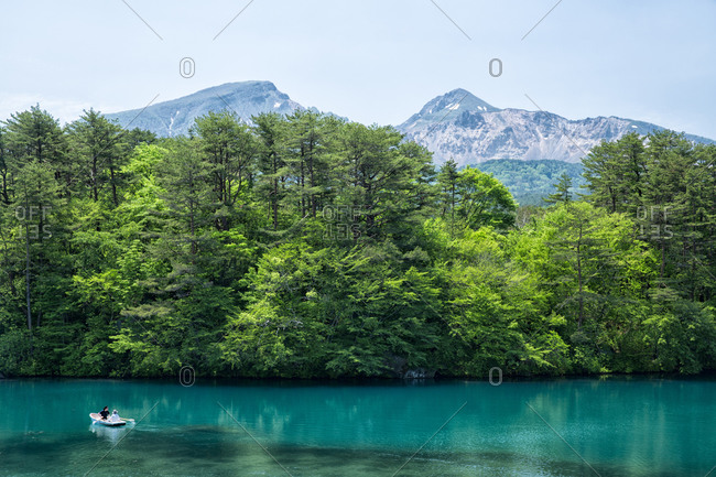 Boaters on a Goshiki-numa lake with a  view of Mount Bandai in Fukushima, Japan
