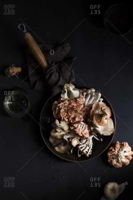 Exotic mushrooms being prepared with champagne, garlic and peppercorns