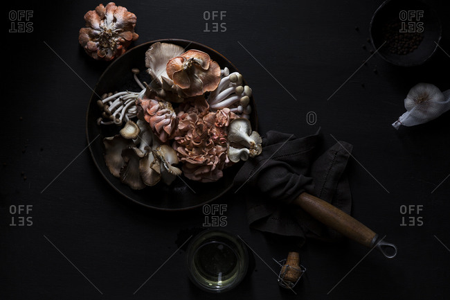 Exotic mushrooms being prepared with garlic, peppercorns and champagne