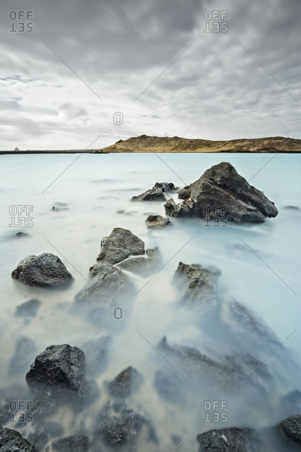 A blue geothermal lake and rocks in Reykjanes, Iceland