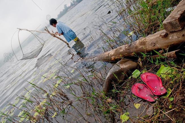 A young boy fishing on Bratan Lake in Indonesia