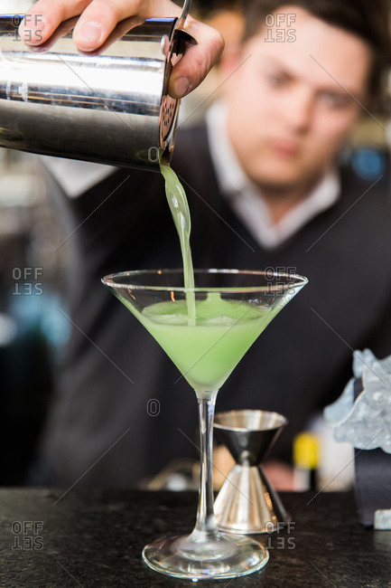 A bartender pours a green drink into a martini glass