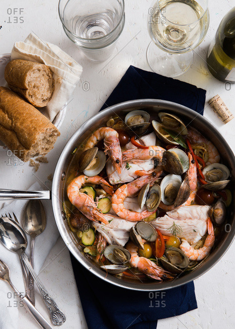 A bouillabaisse served with a loaf of bread and white wine