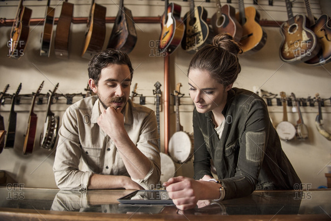 Couple with tablet in instrument store
