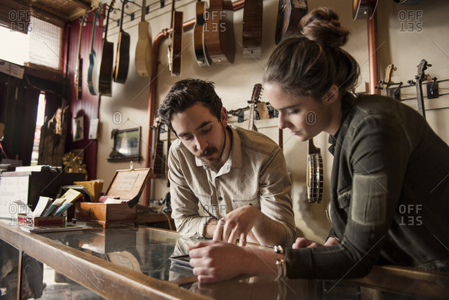 Couple checking tablet in instrument store