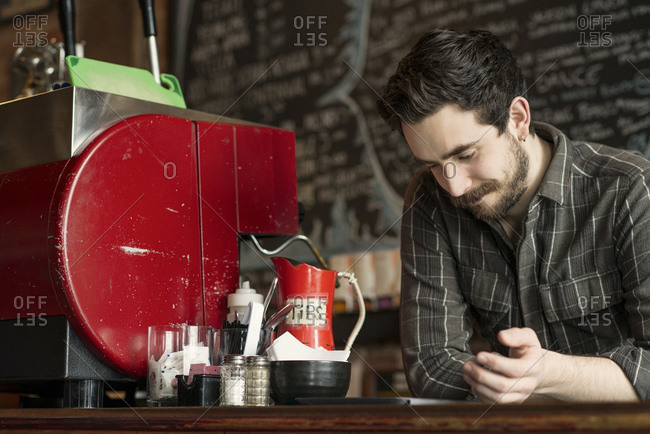 Barista at cafe counter with tablet