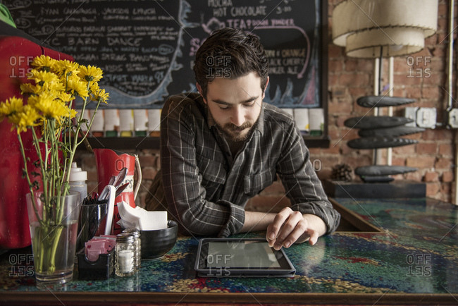 Barista at cafe counter reading tablet