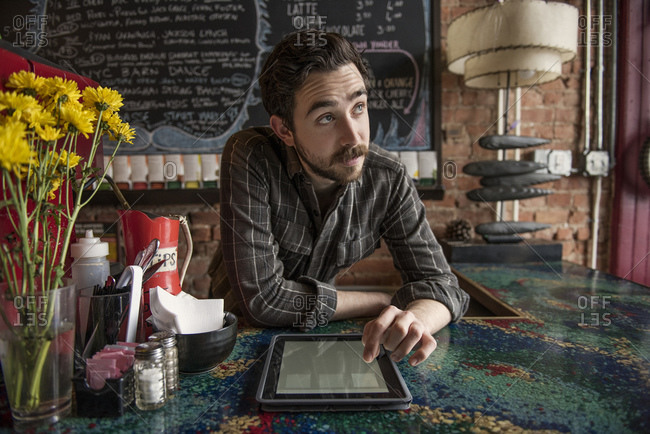 Barista with tablet looking up