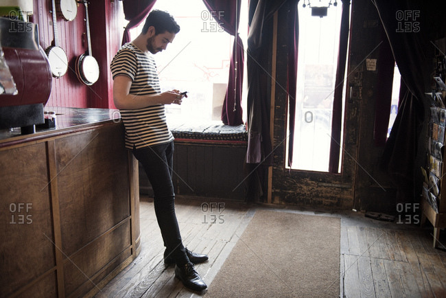 Man standing in cafe with phone