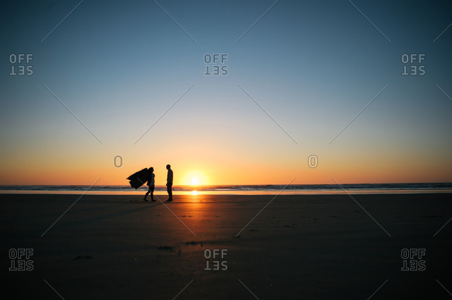 A woman holding a blanket walks up to a man on the beach