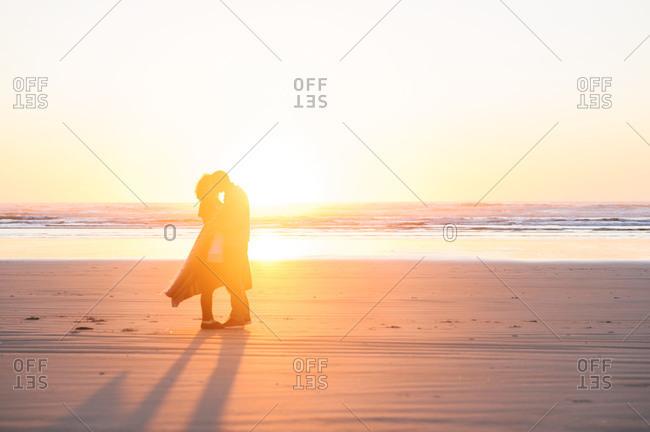 A couple kisses on the beach