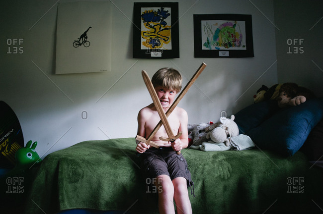 A boy plays with swords in his bedroom