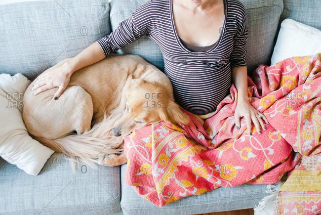 A pregnant woman cuddles with a Labrador Retriever