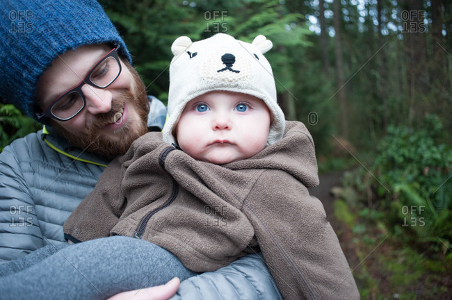 A father holds his baby in the woods in Washington state