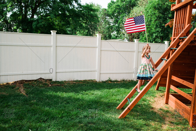 Child climbing up a wooden play structure with an American flag