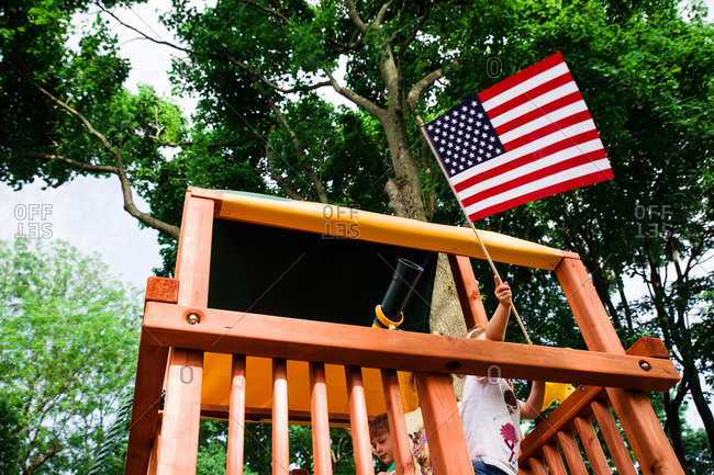 Child waving an American flag out of a play fort