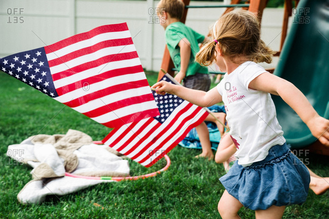 Children running in backyard with American flags