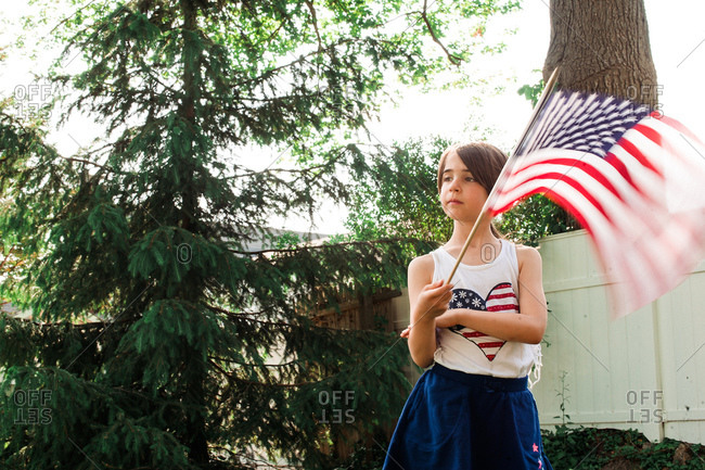 Young girl holding an Amercian flag in backyard