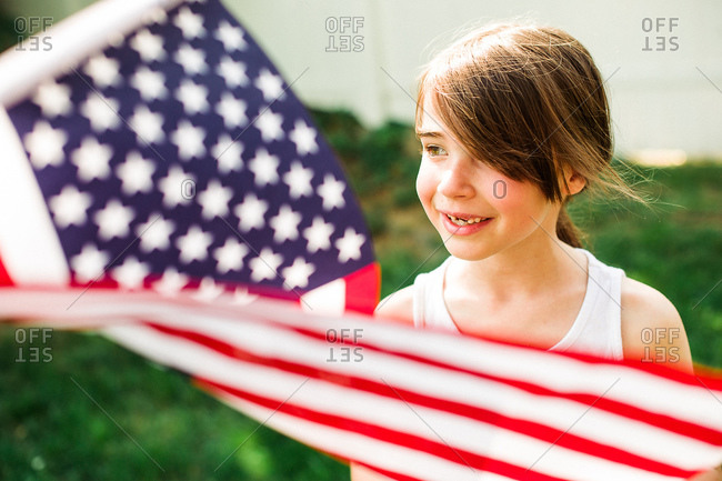 Smiling young girl with an American flag