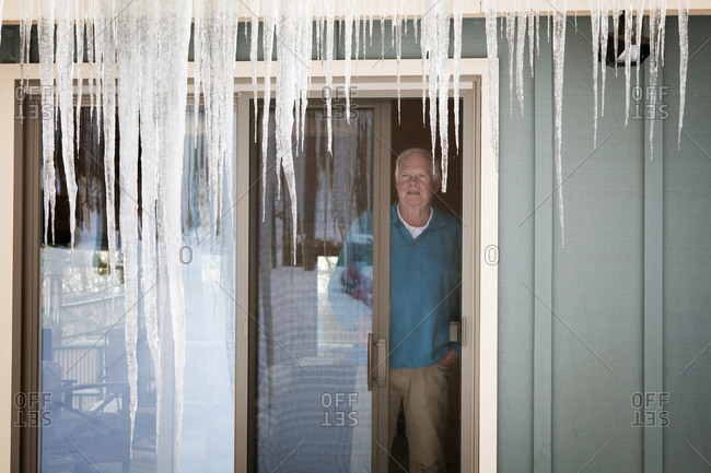 Man looking out at icicles at his home