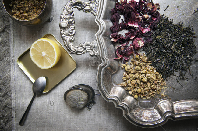 Loose herbal teas and lemon on a silver platter
