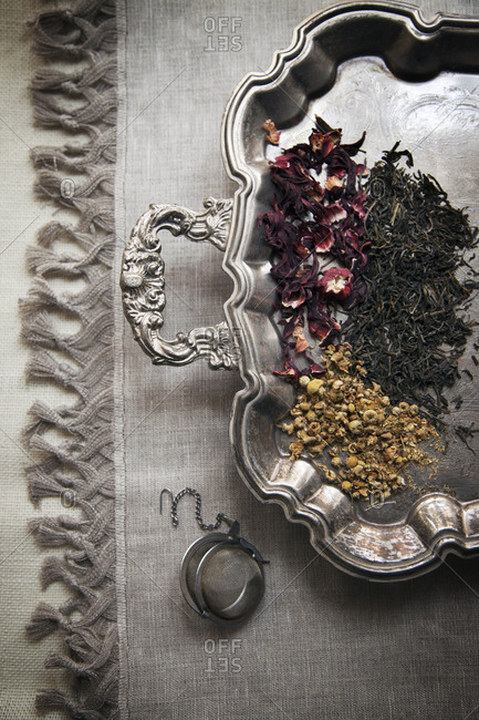 Herbal teas and strainer on a silver platter